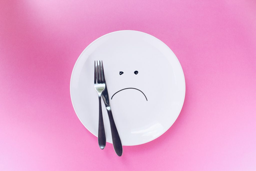 A white plate with an unhappy face, joined by a fork and a knife.