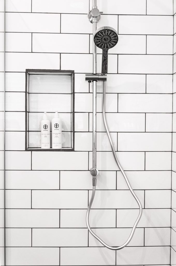 A beautiful white tile shower stall with modern shower head.